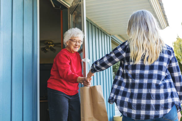 Mature Adult Female Delivering Groceries to Senior Adult Female and Social Distancing Due to Infectious Virus Outbreak Pandemic stock photo