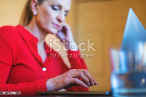 In Western Colorado Mature Adult Female Using and Experiencing Laptop Technology Working from Home Image Series (Shot with Canon 5DS 50.6mp photos professionally retouched - Lightroom / Photoshop - original size 5792 x 8688 downsampled as needed for clarity and select focus used for dramatic effect)