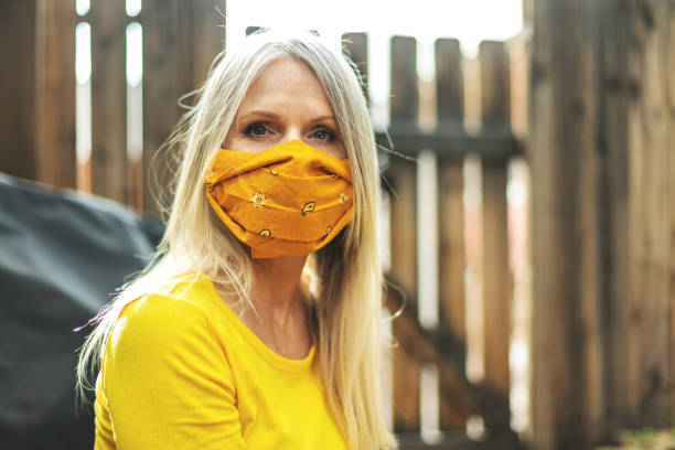 Mature Adult Female Wearing Face Mask and Social Distancing Due to Infectious Virus Outbreak Pandemic stock photo