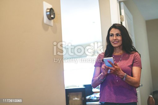 Operating smart Climate Control devices in her home through the use of smart phone Mature Adult Hispanic Female in Western Colorado (Shot with Canon 5DS 50.6mp photos professionally retouched - Lightroom / Photoshop - original size 5792 x 8688 downsampled as needed for clarity and select focus used for dramatic effect)