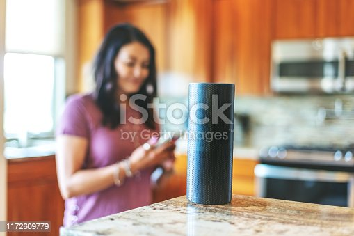 Operating smart speaker devices in her home through the use of smart phone Mature Adult Hispanic Female in Western Colorado (Shot with Canon 5DS 50.6mp photos professionally retouched - Lightroom / Photoshop - original size 5792 x 8688 downsampled as needed for clarity and select focus used for dramatic effect)