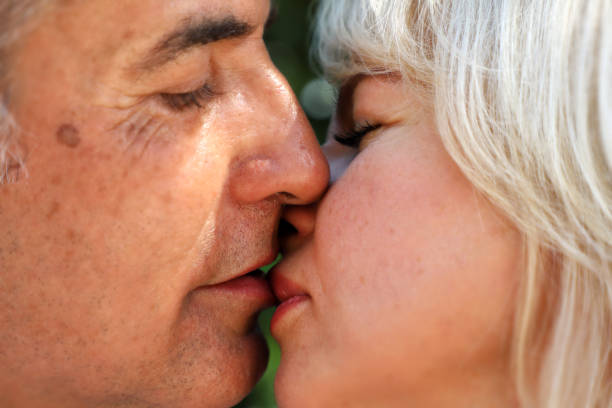 mature adult man and woman in love and kissing stock photo