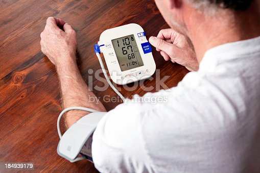 Senior man monitoring his blood pressure at home