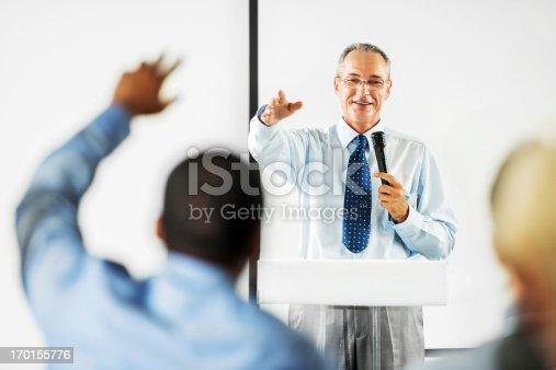 1180973515 istock photo Mature adult man having a public speech. 170155776