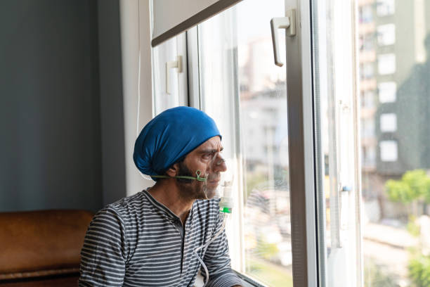Mature Adult Man Using Nebulizer And Looking Through Window stock photo