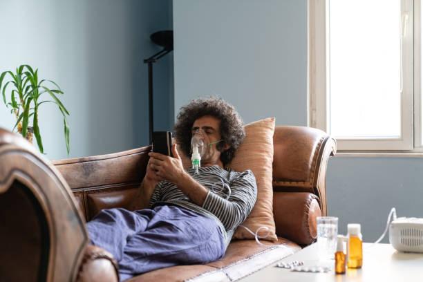 Mature Adult Man Using Nebulizer At Home stock photo
