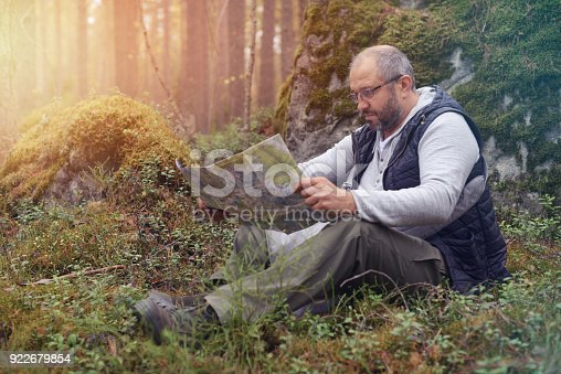 872969580istockphoto Mature Adult man walking in the forest 922679854