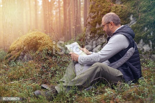 872969580istockphoto Mature Adult man walking in the forest 922696624