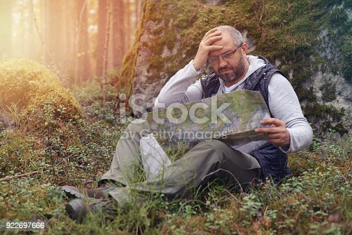 872969580istockphoto Mature Adult man walking in the forest 922697666
