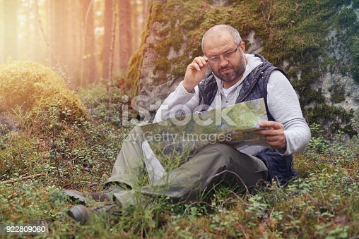 872969580istockphoto Mature Adult man walking in the forest 922809060