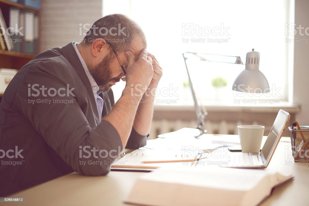 Mature Adult man working in the office stock photo
