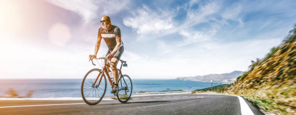 Mature Adult on a racing bike climbing the hill at mediterranean sea landscape coastal road stock photo