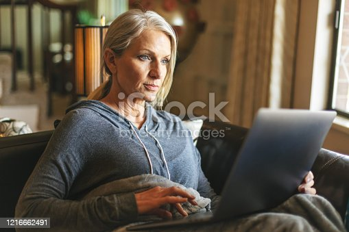 During Infectious Disease Pandemic Mature Adult Pre Senior Female Sheltering In Place Home Activities COVID-19 Image Series with Corona Virus Model in Background (Shot with Canon 5DS 50.6mp photos professionally retouched - Lightroom / Photoshop - original size 5792 x 8688 downsampled as needed for clarity and select focus used for dramatic effect)