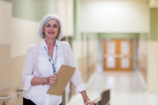Mature adult school counselor takes break in corridor As she goes from her office to the cafeteria, a mature adult counselor takes a break for photo. administrator stock pictures, royalty-free photos & images