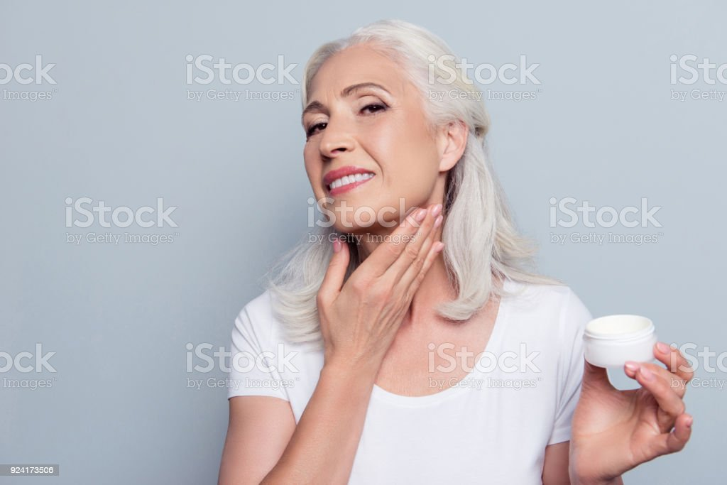 Mature adult senior woman with gray hair is taking care about her face and neck, she is smearing natural night cream using hand before going to bed, isolated on gray background stock photo