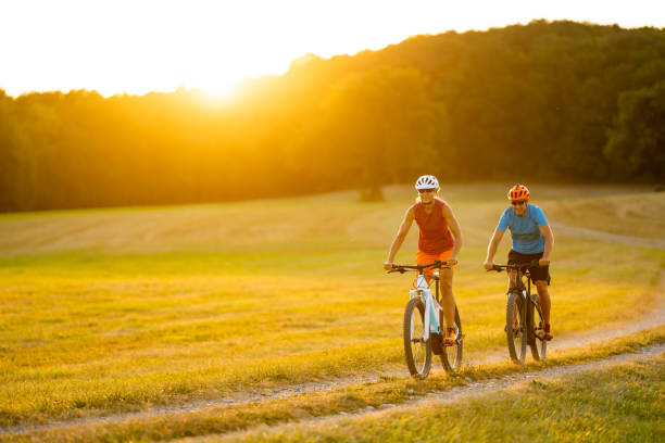 mature adult sporty people cycling in rural landscape at sunset stock photo