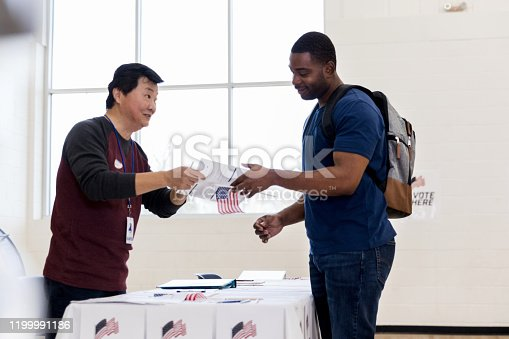 On voting day, the mature adult male volunteer helps the mid adult man sign to vote.