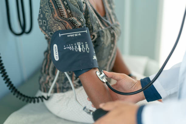 Mature adult woman has blood pressure checked stock photo
