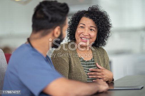 A woman of Asian descent is at a medical consultation. She is sitting at a table next to her doctor. The doctor is a mixed-race man of Asian and Indian descent. The two individuals are having a conversation. The patient is smiling and talking.