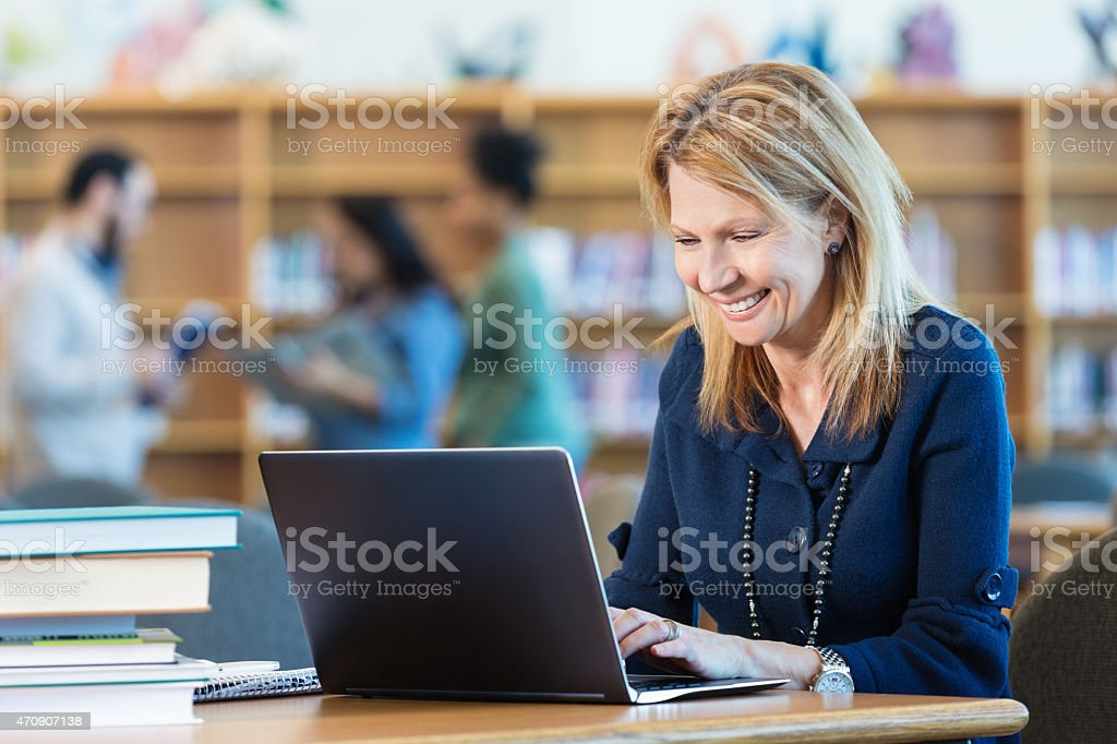 Mature adult woman studying for college class in library stock photo