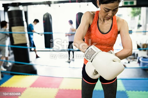 Mature adult woman training at boxing gym