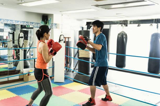 reife erwachsene frau mit männlichen lehrer an boxing gym training - ring anleitung stock-fotos und bilder