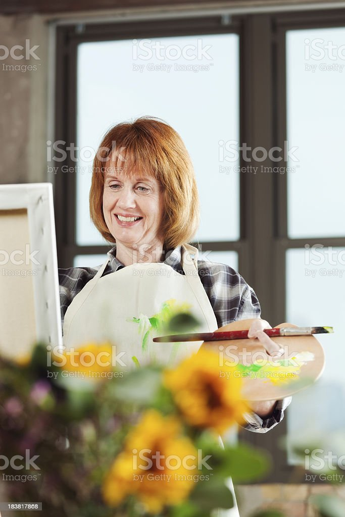 Mature Adult Woman's Hobby, Painting Canvas in Condominium Apartment Home royalty-free stock photo