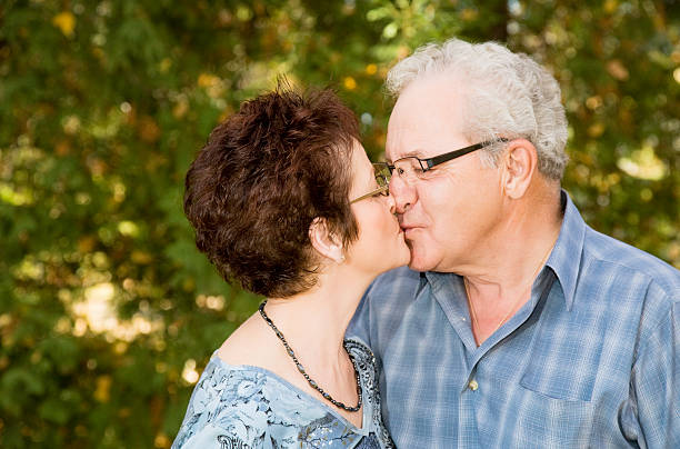 adulti maturi baciare - brunette woman eyeglasses kiss man foto e immagini stock