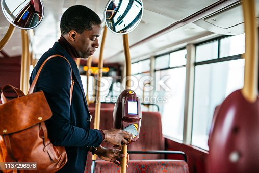 Portrait of smart African-American businessman, on the move, using public transportation while going to work.