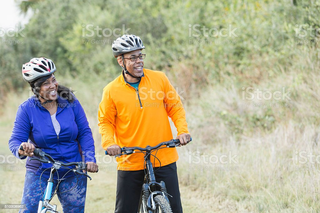 Mature African American couple riding bikes in park stock photo