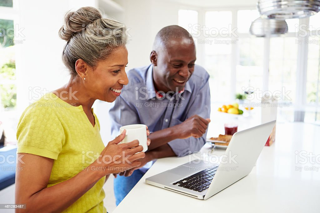 Mature African American couple using a laptop in a kitchen stock photo