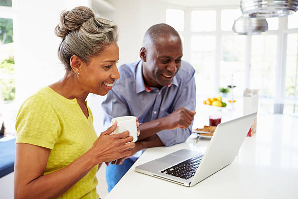 Mature African American couple using a laptop in a kitchen Mature African American Couple Using Laptop At Breakfast mature couple stock pictures, royalty-free photos & images