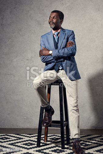 973213156 istock photo mature african american man sitting on stool 973210482