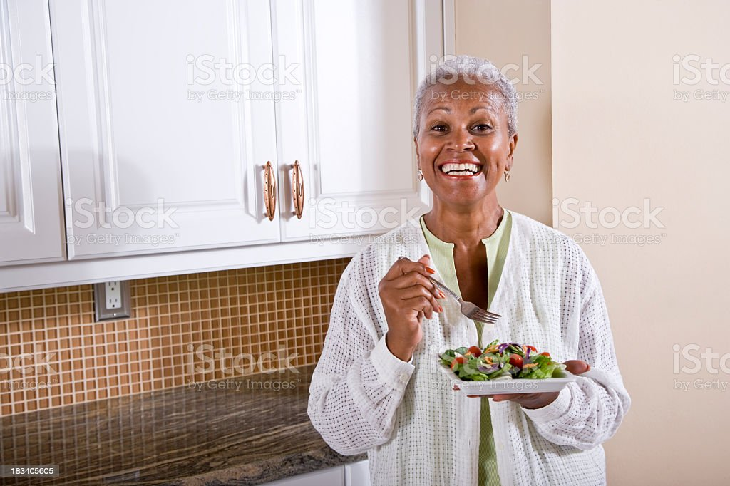 Mature African American woman eating salad in kitchen stock photo