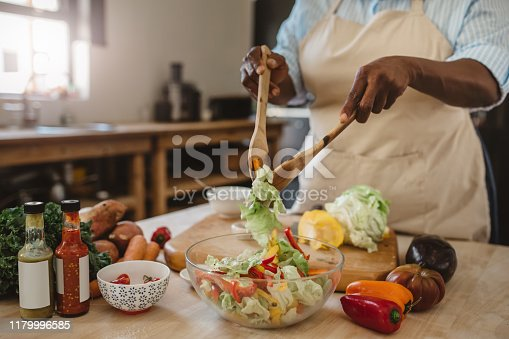 Cropped closeup of an African American woman standing at a counter in her kitchen at home mixing a delicious salad