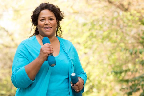 reife afroamerikanische frau lächelnd und trainieren. - joggerin stock-fotos und bilder