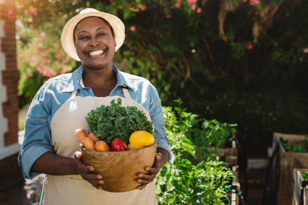Mature African American woman smiling and holding fresh vegetables outside stock photo