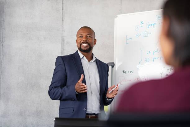 Mature african businessman training employees stock photo
