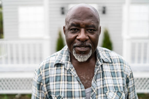 Mature african man standing outdoors and looking at camera Mature african man standing outdoors, in front of his hoouse. 65 69 years stock pictures, royalty-free photos & images