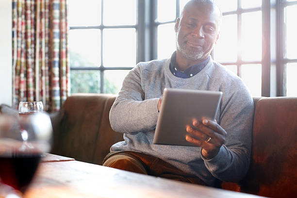 Mature african man using tablet pc in a pub Mature african man sitting in a pub using digital tablet old man working in a pub stock pictures, royalty-free photos & images
