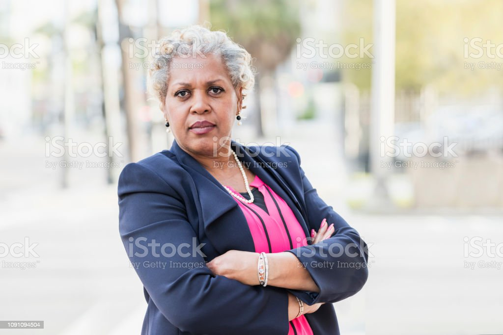 A mature, professional African-American businesswoman standing...