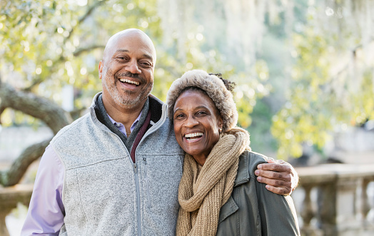 Headshot of a mature African-American couple taking a walk in the park on a sunny fall day. The man is in his 50s, and his wife is a senior, in her 60s. They are standing together, smiling at the camera.