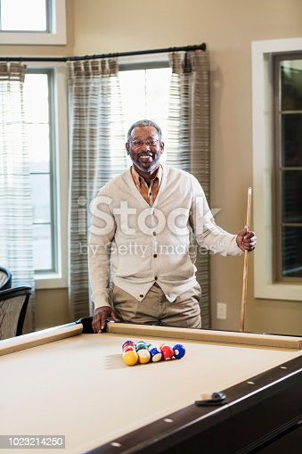 A mature African-American man in his 50s playing billiards. He is standing at one end of the pool table, holding a cue stick, ready to start the game.