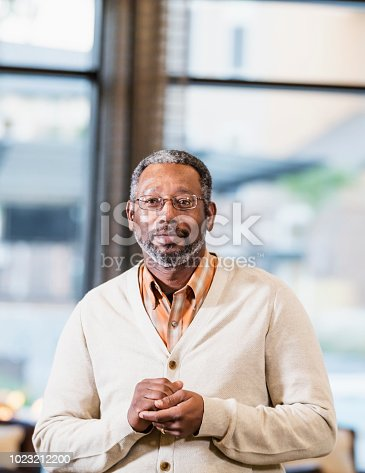A mature African-American man in his 50s standing indoors near a window. He is wearing eyeglasses and a cardigan sweater, looking at the camera with a serious, confident expression.