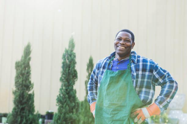 reife afrikanisch-amerikanischer mann arbeitet in gärtnerei - gartenarbeit stock-fotos und bilder