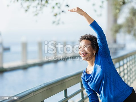 istock Mature African-American woman exercising on waterfront 950961948