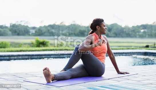 A mature African-American woman in her 50s sitting on a pool deck on an exercise mat, stretching.