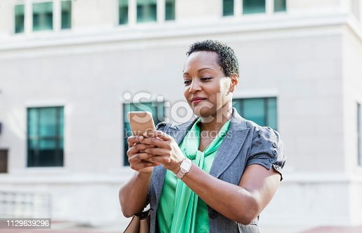 istock Mature African-American woman in city texting 1129639296