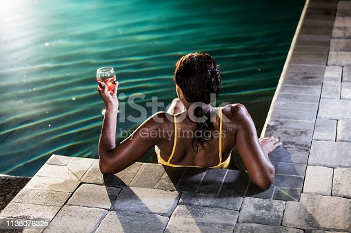 istock Mature African-American woman in swimming pool with wine 1138076325
