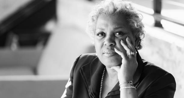 Mature African-American woman looking at camera A mature African-American woman in her 50s sitting in an office, looking at the camera with a serious, perhaps confused, expression on her face. black and white stock pictures, royalty-free photos & images